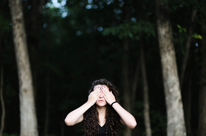 A women in the wood covering her eyes.