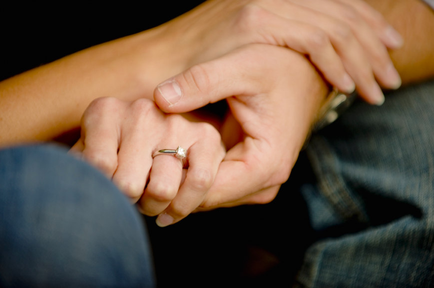 A close up of a couple holding hands.